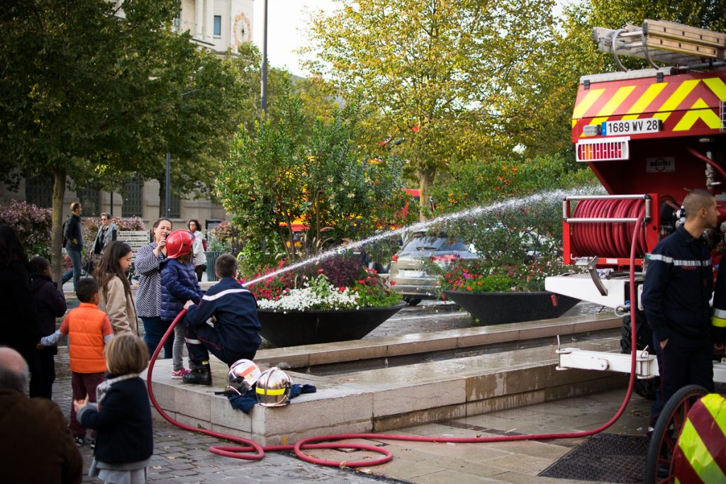 Firemen showing a little kid how to use the hose